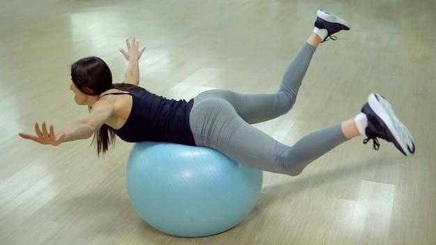 Novato em esportes. jovem mulher fazendo exercícios com bola de ginástica.