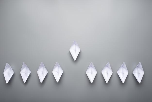 Nove barcos de origami de papel feitos sobre fundo cinza, um conduzindo o outro em uma imagem conceitual.