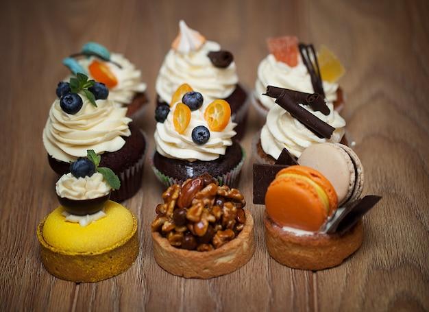 Nove bolos diferentes em pé sobre uma mesa de madeira