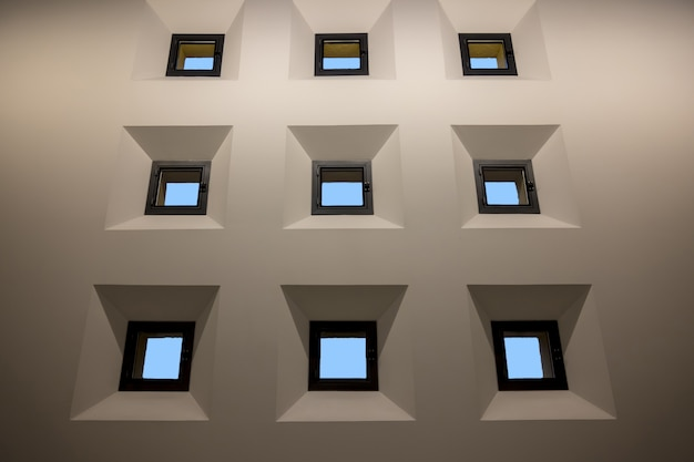 Nove pequenas janelas isoladas na parede branca