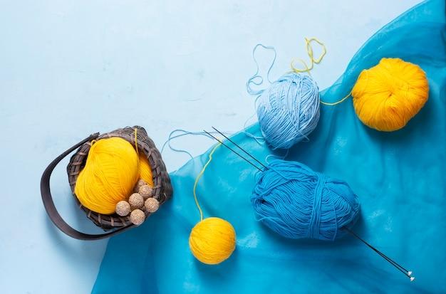 Novelas de fios azuis e amarelos repousam sobre um fundo azul claro, próximo a elas há uma cesta de vime.