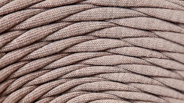 Novelo de close-up de fio de malha cinza. macro fotografia fundo textura padrão tecer fibra têxtil tecido. tiras de tecido são entrelaçadas em um carretel.