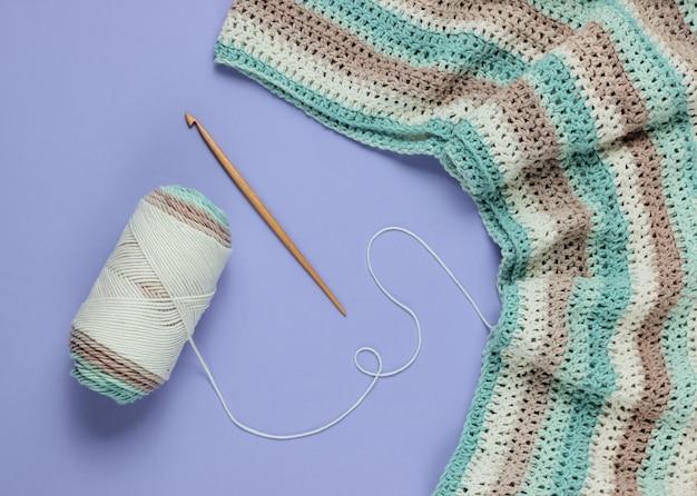 Novelo de fios de lã com fio e agulha de crochê de madeira no fundo roxo