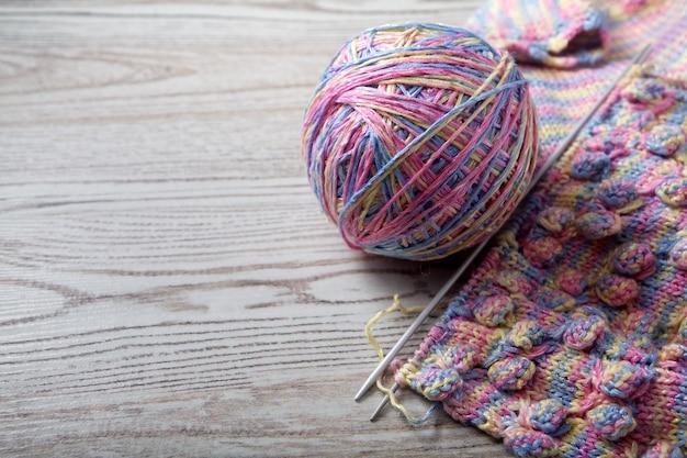 Novelo de lã e tricô em uma mesa de madeira