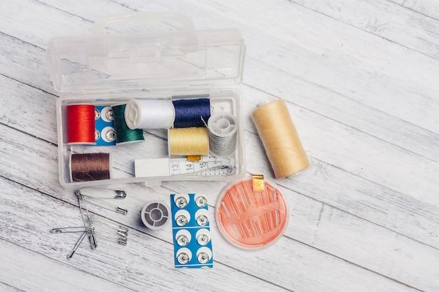 Novelo de linha multicolorida em uma caixa de plástico de agulhas de parede de madeira suprimentos de costura alfinetes.