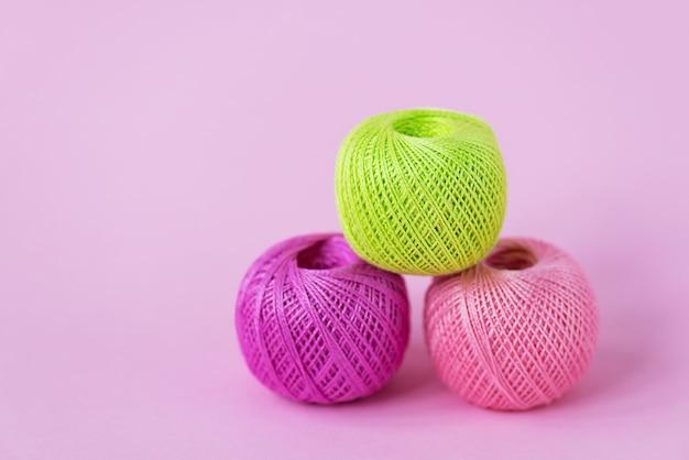 Novelos de linha para tricô em fundo rosa