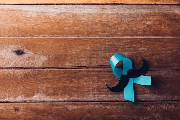 Novembro, azul, fita azul claro com um bigode masculino em fundo de madeira, conscientização sobre a saúde dos homens, conscientização sobre o câncer de próstata
