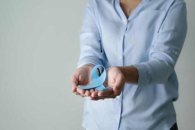 Novembro fita azul claro na mão da mulher mês de conscientização do câncer de próstata