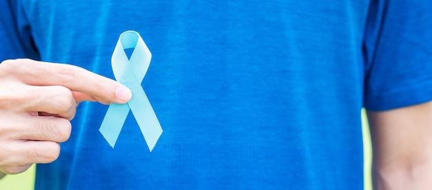 Novembro mês de conscientização do câncer de próstata, homem de camiseta azul com a mão segurando a fita azul para apoiar as pessoas que vivem e doenças. cuidados de saúde, homens internacionais, conceito do dia do câncer pai e mundial