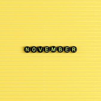 Novembro miçangas palavra tipografia em amarelo