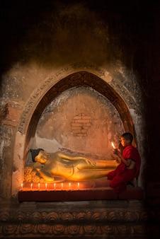 Noviço de mianmar reza a estátua de buda na cidade velha de bagan, bagan, mianmar
