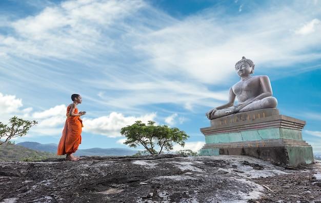 Noviço monge rezando para o buda no templo phrabuddchachay, saraburi, tailândia