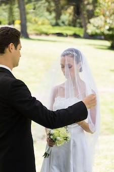 Novio prestes a levantar o véu da noiva