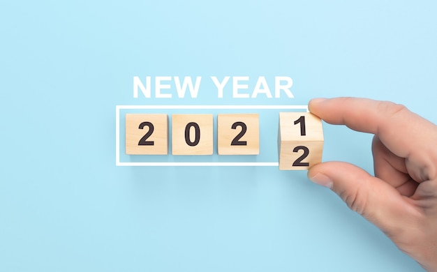 Novo ano de 2021 mudar para o conceito de 2022 virar a mão sobre o bloco de cubos de madeira virar cubos de madeira