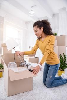 Novo apartamento. garota otimista de cabelos cacheados tirando um abajur da caixa enquanto desfazia seus pertences, tendo se mudado para um novo apartamento