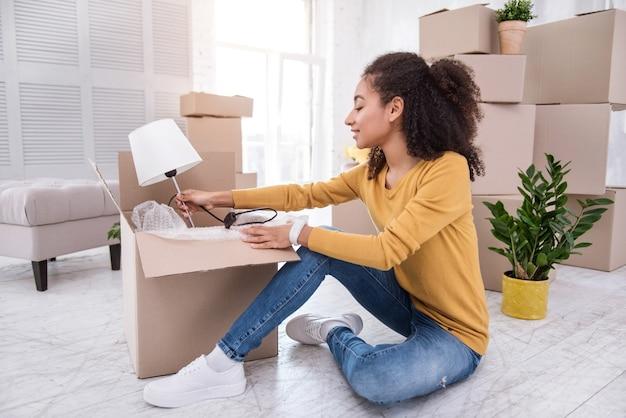 Novo apartamento. menina agradável de cabelos encaracolados abrindo a caixa de um abajur e sorrindo, tendo se mudado para um novo apartamento