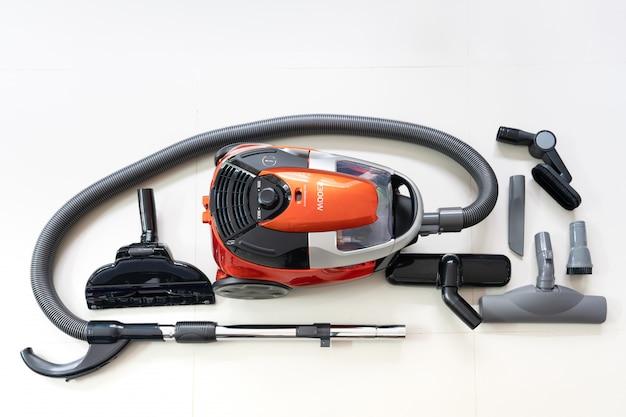 Novo aspirador de pó e cabeças de escova de limpeza no piso de ladrilho branco