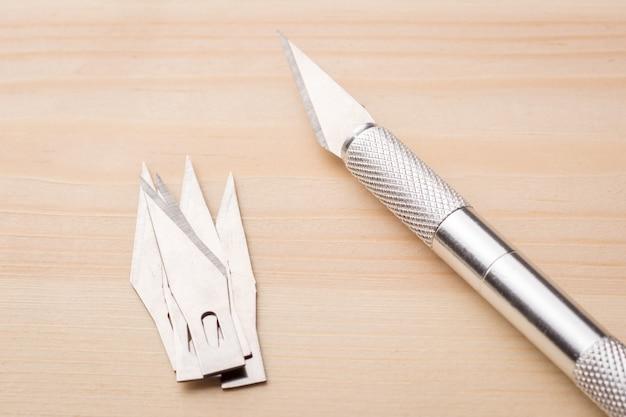 Novo bisturi profissional e lâminas na mesa de madeira