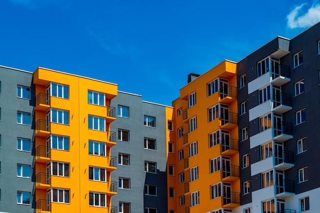 Novo bloco de apartamentos modernos com varanda e céu azul ao fundo