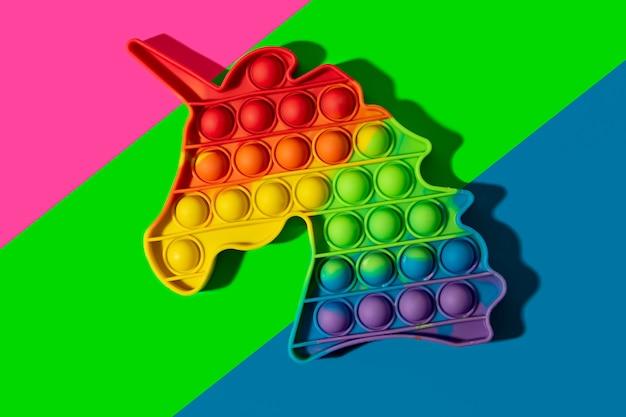 Novo brinquedo de silicone em forma de unicórnio no fundo multicolor de néon.