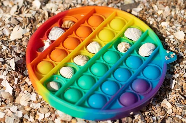 Novo brinquedo de silicone estalando na praia com conchas em um conceito criativo. brinquedo de antistress