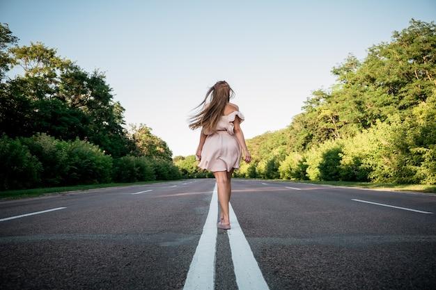 Novo caminho, novo começo, resolução de ano novo, desafio, escolha ou conceito de mudança. mulher jovem caminhando na estrada de verão com árvores ao redor.