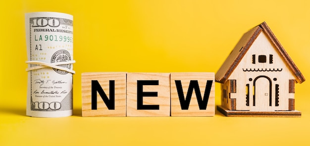 Novo com modelo em miniatura de casa e dinheiro em um fundo amarelo