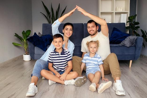 Novo conceito de compra de apartamento de edifício residencial. família cheia de estilo com dois filhos sentados no tapete, mamãe e papai fazem uma figura