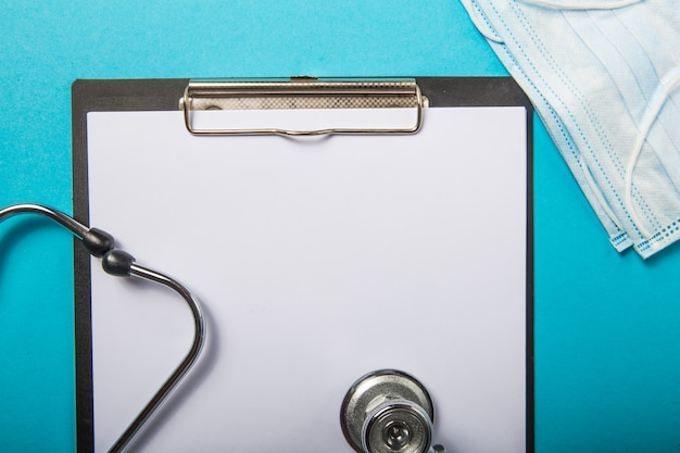Novo conceito de coronavírus 2019-ncov. máscara de respiração protetora médica, estetoscópio sobre fundo azul claro, vista superior.