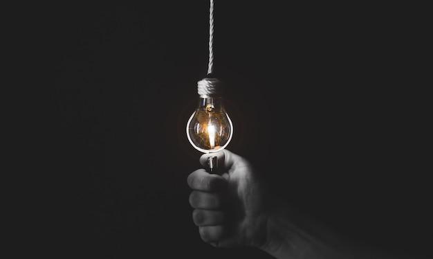 Novo conceito de ideia. homem está segurando o iluminador perto da lâmpada. foto em preto e branco.