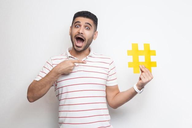Novo conceito de mídia social. positivo jovem adulto em t-shirt segurando um grande grande sinal de hashtag amarelo e apontando com o dedo com uma cara incrível. interior, isolado, foto de estúdio, fundo branco