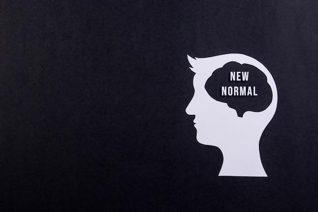 Novo conceito normal após pandemia de covid-19. cabeça humana com texto em fundo preto.