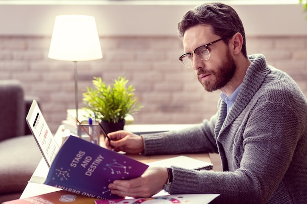 Novo conhecimento homem inteligente e simpático lendo um livro sobre astrologia enquanto faz seu trabalho