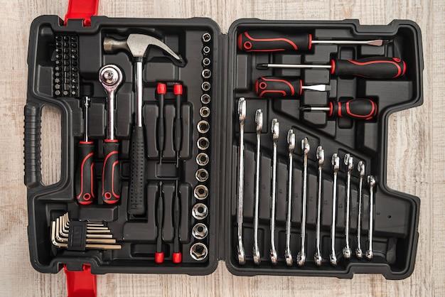 Novo conjunto de chaves e brocas na caixa de ferramentas na mesa de madeira