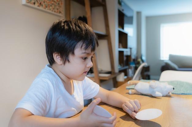 Novo estilo de vida normal, criança jogando cartas de papel na sala de estar com luz forte pela manhã