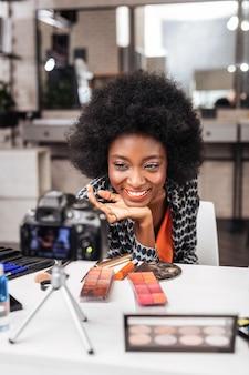 Novo estilo. mulher sorridente com um top laranja demonstrando nova maquiagem enquanto conduz um tutorial online