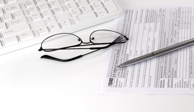 Novo formulário fiscal irs 1040, instruções, caneta, teclado e óculos. copie o espaço