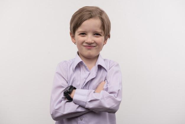 Novo gadget. garoto feliz e fofo parado de mãos cruzadas usando um smartwatch