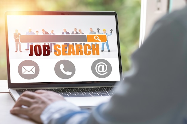 Novo graduado usando laptop procura por novos empregos online no site head hunters. conceito de recrutamento.