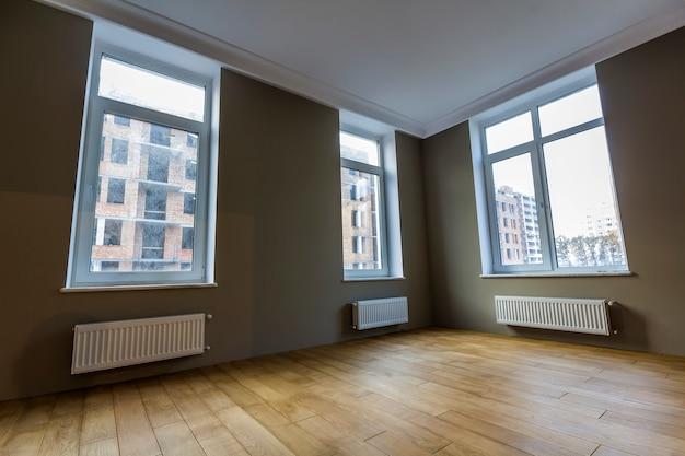 Novo interior do quarto renovado, com grandes janelas, radiadores de aquecimento e piso em parquet de madeira