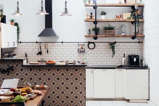 Novo interior leve e moderno da cozinha com móveis brancos.