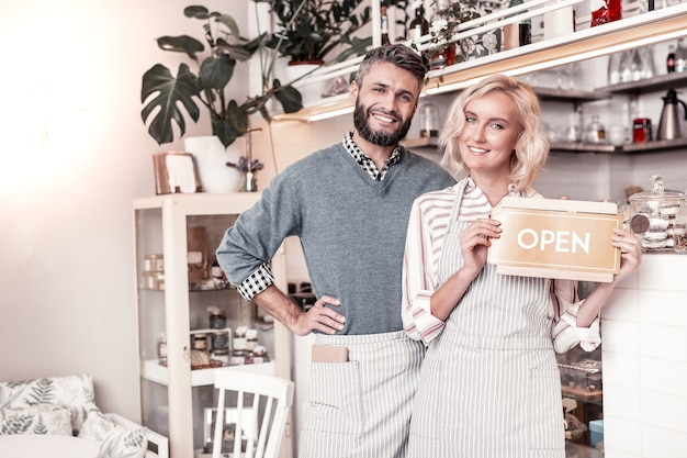 Novo lugar. casal feliz e encantado em pé juntos em frente ao balcão enquanto abrem seu próprio café