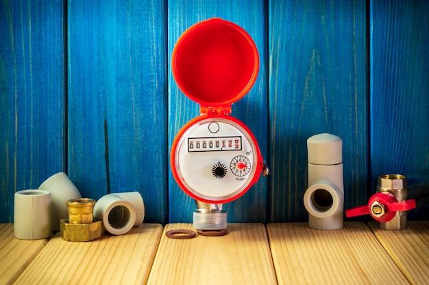 Novo medidor de água com acessórios em um fundo de madeira vintage.