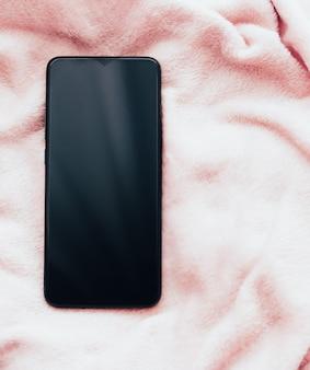 Novo modelo de telefone móvel em maquete de flatlay de smartphone de fundo de tecido rosa suave como modelo de aplicativo e ...