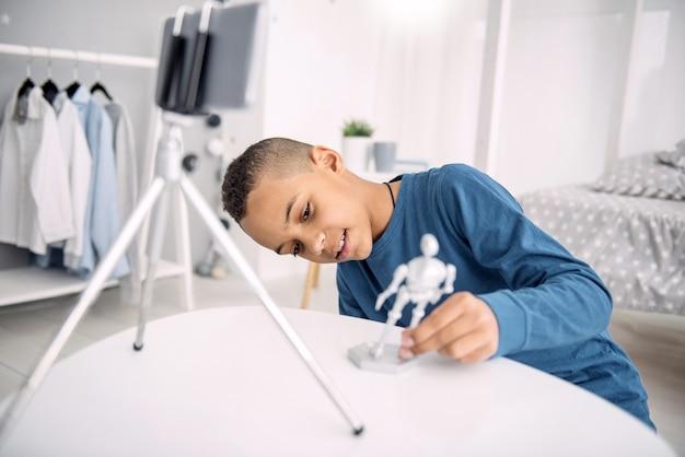 Novo modelo. que bom que blogueiro afro-americano gravando vídeo enquanto examina o brinquedo