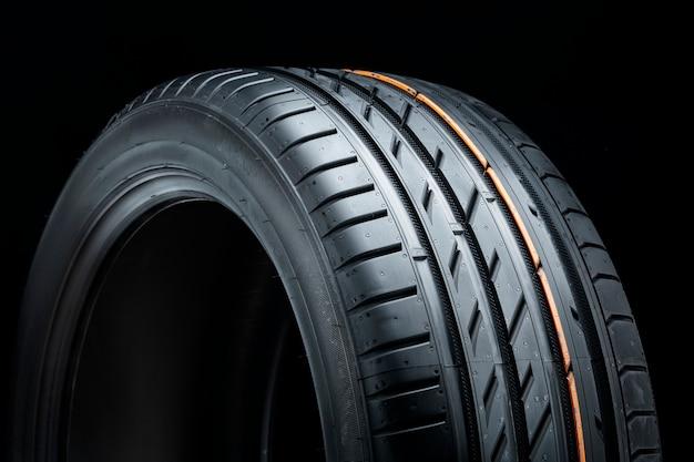 Novo pneu de verão, close-up do piso em superfície preta