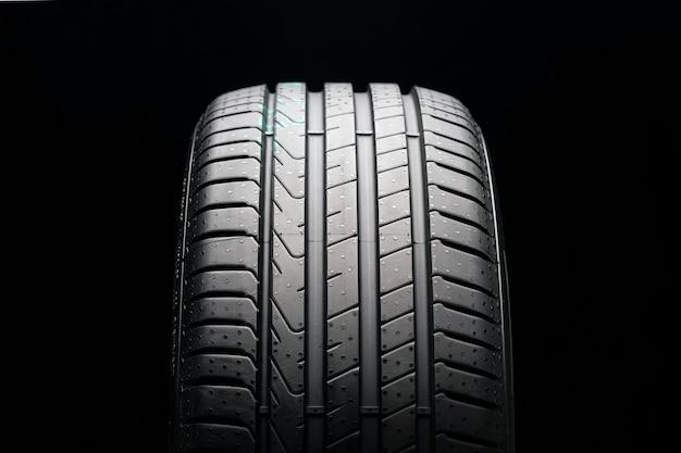 Novo pneu de verão em um fundo preto