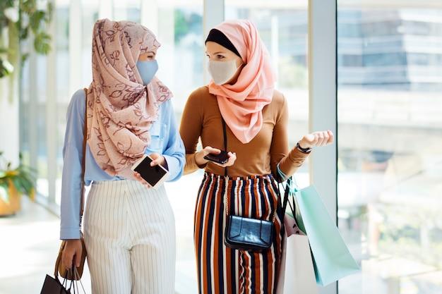 Novo ponto de encontro normal, amigos muçulmanos usando máscara