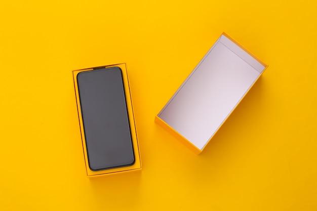 Novo smartphone moderno em uma caixa de embalagem em amarelo. minimalismo.
