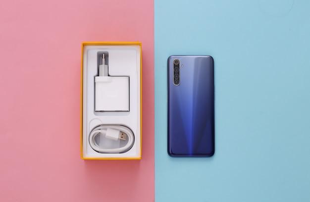 Novo smartphone moderno em uma caixa de embalagem em rosa azul pastel